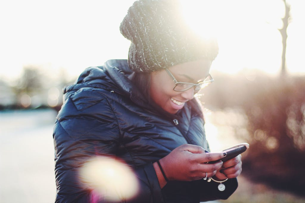 Woman in winter coat smiling and checking SMS